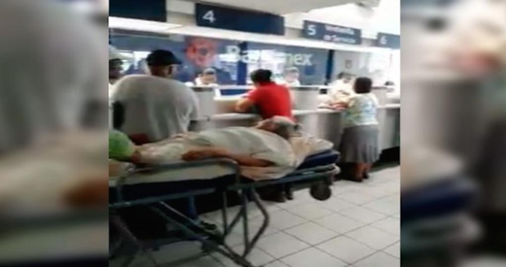 Anciana va en camilla a un banco para poder cobrar su pensión